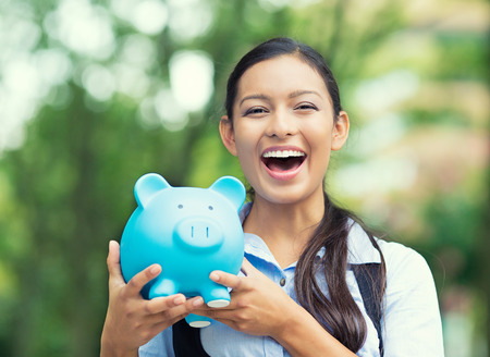 creditor: Closeup portrait happy, smiling business woman, bank employee holding piggy bank, isolated outdoors indian autumn background. Financial savings, banking concept. Positive emotions, face expressions Stock Photo
