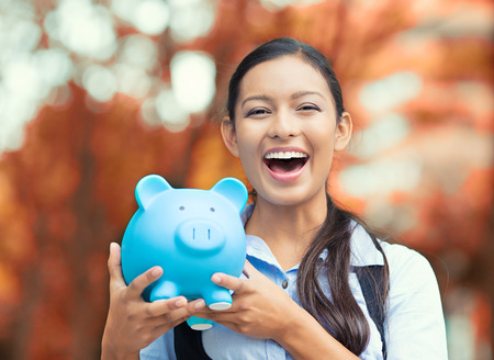 Closeup portrait happy, smiling business woman, bank employee holding piggy bank, isolated outdoors indian autumn background. Financial savings, banking concept. Positive emotions, face expressions Stock Photo