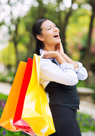 Portrait Shopping woman in Washington DC City. Beautiful model happy, smiling summer shopper holding shopping bags walking outside background outdoor park. Positive emotions, facial expressions. photo