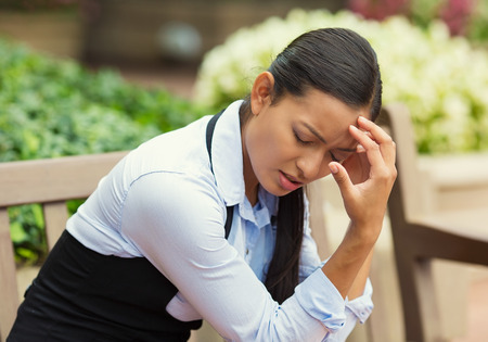 Closeup portrait unhappy business woman head on hand sitting on park bench bothered by mistake having bad headache isolated background outdoor office. Negative human emotion, facial expression feeling photo