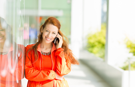 uptown: Portrait happy smiling woman talking on mobile cell phone standing outdoor her university. Business woman having conversation on cellphone isolated outside office background. Communication concept