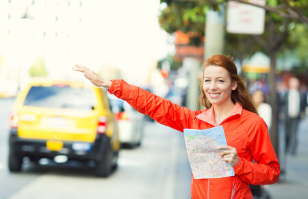 hailing: Girl calling taxi cab in New York City, holding city map standing on sunny summer day in street of Manhattan, USA. Beautiful young woman outdoor on her vacation trip. Positive face expression, emotion Stock Photo