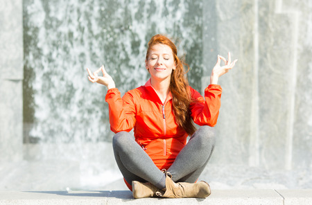 Portrait beautiful woman meditating yoga in lotus position isolated outdoors park waterfall background. Urban life style, stress relief techniques. Positive facial expression, emotion, life perception