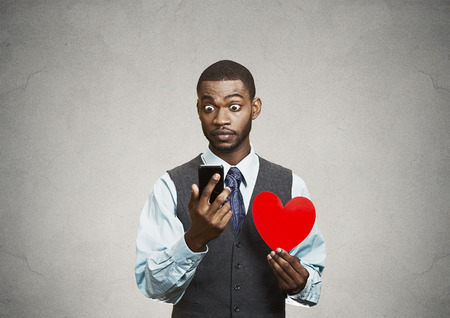 Closeup portrait puzzled young man reading breaking news on smart phone, holding red heart in his hand, isolated grey wall background. Human facial expressions, emotions, feelings, body language. photo