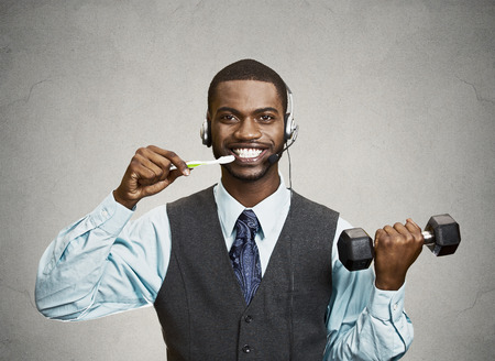 simultaneous: Concept of multitasking businessman. Closeup portrait corporate business man talking on phone, brushing teeth, lifting dumbbell isolated grey wall background. Face expression, emotion. Phone addiction