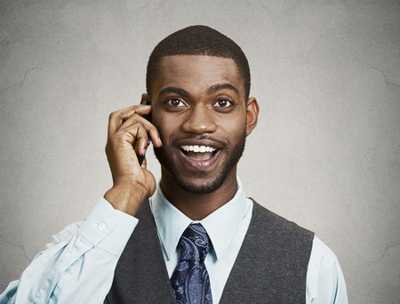 Closeup portrait happy business man talking on mobile phone, isolated grey wall background. Positive human facial expressions, emotions, feelings, life perception, attitude, thinking photo