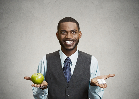 Closeup portrait young fit happy executive man holding green fresh apple in one hand, pills, vitamins in another, trying to decide which choice is the best one. Face expressions, emotions, health care