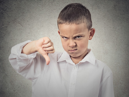 delusion: Portrait unhappy, Angry, Displeased Child giving Thumbs Down hand gesture, isolated grey wall background. Negative human Face Expressions, Emotions, Feelings, attitude, life perception, body language