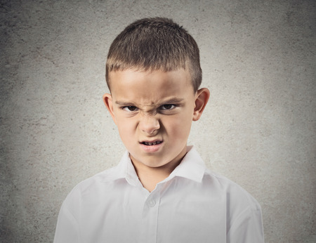 Closeup portrait Angry, displeased child Boy looking at you camera, mad about something, isolated grey wall background. Negative human emotions, feelings, facial expression, perception, body language photo