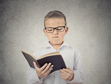 Closeup Portrait Unhappy Child, Boy holding Reading Book, displeased with story, information provided, isolated grey Wall Background. Negative human facial expression, emotions, feeling, body language photo