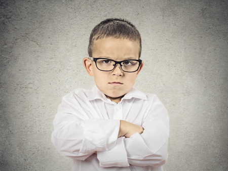 Closeup portrait Angry, displeased child Boy looking at you camera, arms folded, insists on his position isolated grey wall background. Negative human emotions, feelings, facial expression, perception photo