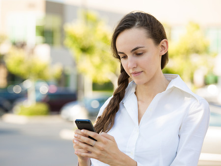 slow: Important Text Message. Portrait Teenage girl looking concerned with text message on her phone, isolated outdoor street background. Human face expressions, emotions, body language, reaction, feelings