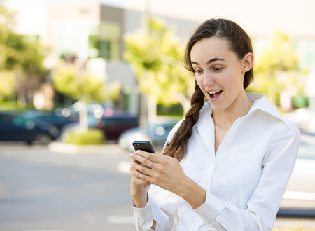 SMS. Portrait funny young businesswoman reading news, text message. Beautiful young caucasian woman isolated outdoor street background holding her smart phone. Human face expression, emotion, reaction photo