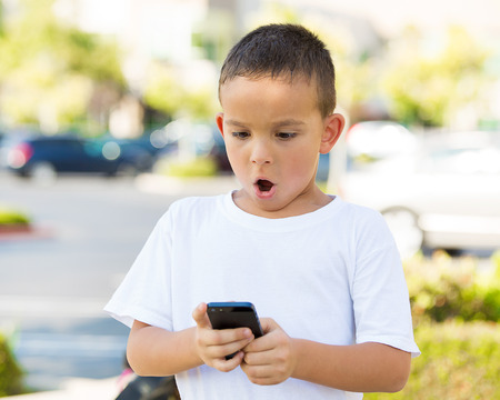 surprised man: Portrait child, surprised boy, little man texting on mobile using smart phone isolated outdoor, outside background. Funny looking human face expression, emotion, reaction, body language. Communication Stock Photo
