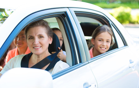 Portrait happy, smiling Family, mother, three kids sitting in the white, silver car looking out windows, ready for vacation trip, outdoor background. Positive Human face expression, emotions, feelings