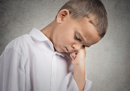 Closeup portrait very sad, depressed, alone disappointed child resting his face on hands, isolated grey wall background  Negative human emotion, face expression, feeling, life perception body language photo