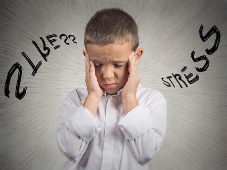 Closeup portrait stressed child, boy hands on temples, head spinning around, overwhelmed at school in life, isolated grey wall background  Human facial expressions, emotions, feeling, perception photo