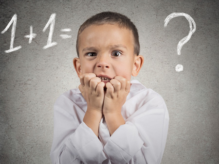 uneducated: Problem  Closeup portrait anxious, funny looking boy, trying to solve math assignment, isolated grey wall background  Human face expressions, emotions, feelings, body language, life perception Stock Photo