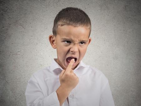 Close-up portret ongelukkig boos, geërgerd pissig jongen met vinger in de mond kijken met grappige gezicht negatieve uitdrukking, afkeuring, geïsoleerde grijze muur achtergrond Menselijke emotie teken, lichaamstaal