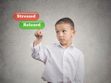 tense: Closeup portrait young man picking touching with finger relaxed green button vs red stressed button on imaginary touch screen display isolated grey wall background  Emotion facial expression reaction