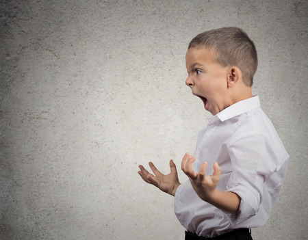 bad behavior: Closeup Headshot side view Portrait Angry Child Screaming, fists up in air isolated grey wall background  Negative Human face Expressions, Emotion, Reaction, Perception  Conflict confrontation concept