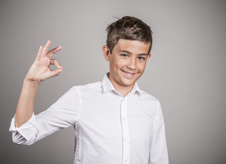 nonverbal communication: Portrait young happy man, teenager showing Ok sign, hand gesture, isolated grey wall background. Positive human emotions, facial expressions, nonverbal communication, body language, signs, symbols