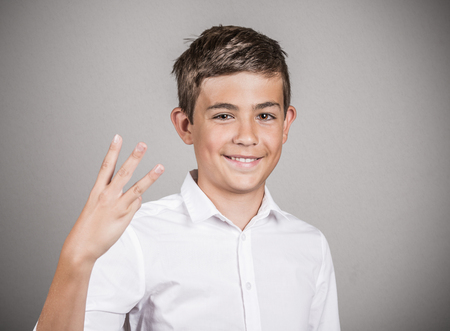 trilogy: Closeup portrait, young handsome, smiling man, student giving three fingers sign gesture with hands, isolated grey wall background. Positive human emotions, facial expressions, feeling, signs, symbol