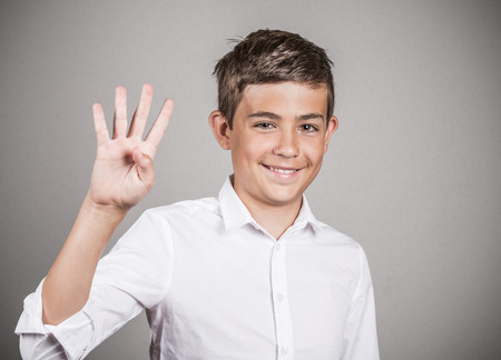 Closeup portrait excited happy young man showing 4 fingers, giving number four sign isolated grey wall background. Positive emotion face expression feeling attitude, reaction, perception body language photo