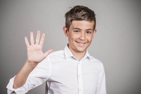 appraising: Closeup portrait, headshot happy, smiling young man making five times sign gesture with hand fingers isolated grey wall background. Positive human emotion, facial expression symbol, body language sign