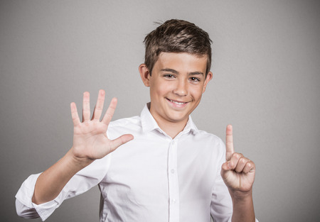 graduation countdown: Closeup portrait excited happy young man showing 6 fingers, giving number six sign, isolated grey wall background. Positive human emotion, face expression, attitude, reaction, perception body language