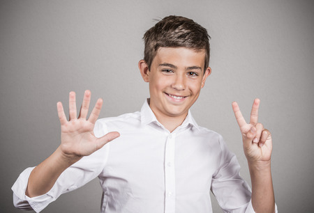 numero: Closeup portrait excited, successful young man giving number 7 hand gesture, showing seven fingers isolated grey background. Positive emotion face expression, signs, reaction non verbal body language Stock Photo