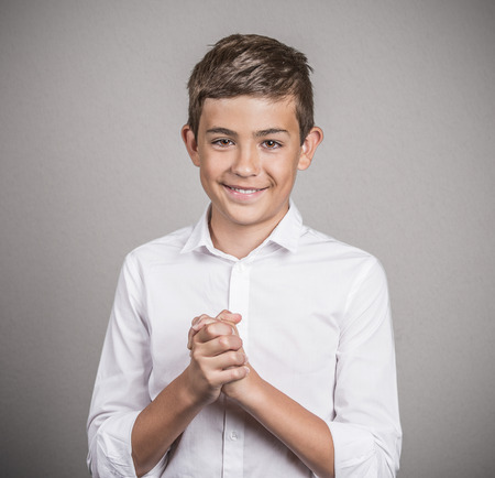 obliged: Closeup portrait young man, handsome student with hands clasped grateful, thankful gesture looking at you camera isolated grey wall background. Positive human emotion, facial expression, body language Stock Photo