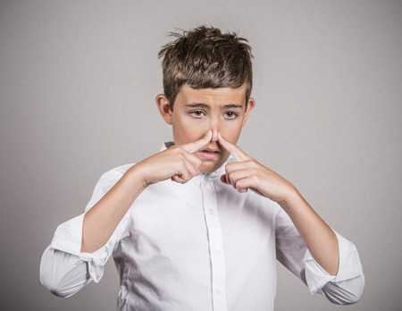 stinks: Closeup portrait young man with disgust on face, pinches his nose, something stinks, bad smell, situation isolated grey wall background. Negative emotions, facial expressions, perception body language Stock Photo