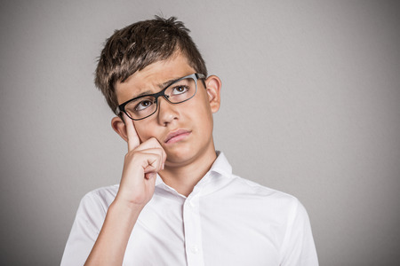 Closeup portrait headshot young man daydreaming looking up, finger on temple gesture, isolated grey wall background, blackboard. Human facial expressions, emotions, feelings, body language, perception photo