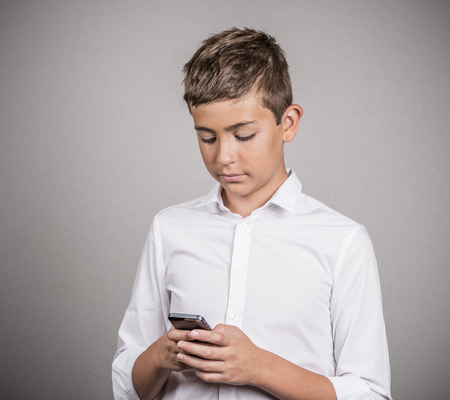 Important Text Message. Portrait Teenage boy looking on screen, reading text message on his phone, isolated grey wall background. Human face expressions, emotions, body language, reaction, feelings Banque d'images