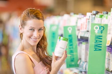 배경 식료품, 약국 상점 선반에 고립 아름 다운 젊은 여자 따기 다이어트 보충제 미소 근접 촬영 초상화, 행복,. 건강한 라이프 스타일 개념입니다. 긍