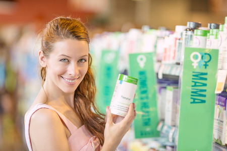 Closeup portrait, happy, smiling beautiful young woman picking diet supplements isolated background grocery, pharmacy store shelves. Healthy lifestyle concept. Positive face expression emotion feeling