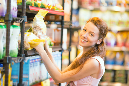 Closeup portrait Beautiful attractive young, happy, smiling Woman shopping for cereal, bulk in grocery supermarket. Positive facial expressions, emotions, feelings. Customer satisfaction concept photo