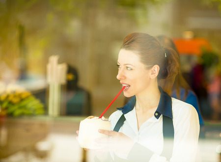 Cafe city lifestyle woman drinking coconut juice looking outside through glass window, sitting indoor in trendy juice bar. Cool young modern female model in her 20s. Positive face expression, emotion photo