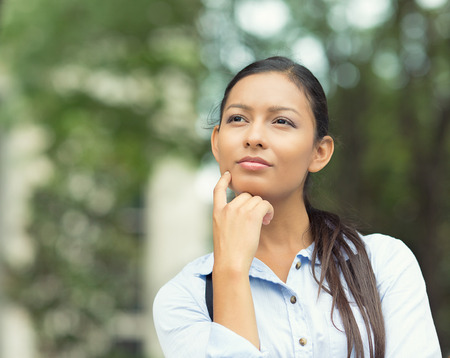 Closeup portrait charming, smiling joyful happy young business woman looking upwards daydreaming something, thinking isolated outdoor park trees background. Positive human emotions, facial expression photo