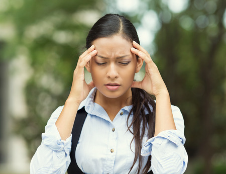 bothered: Closeup portrait unhappy young business woman hands on head stressed bothered by mistake having bad headache migraine isolated outdoor park background. Negative human emotion facial expression feeling