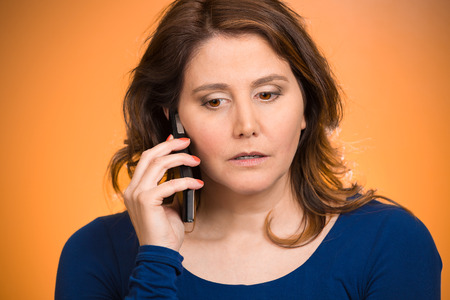 phone conversations: Young sad woman talking on mobile phone upset, depressed, unhappy, worried, isolated orange background. Negative human emotions, facial expressions, feelings, life perception, reaction. Bad news