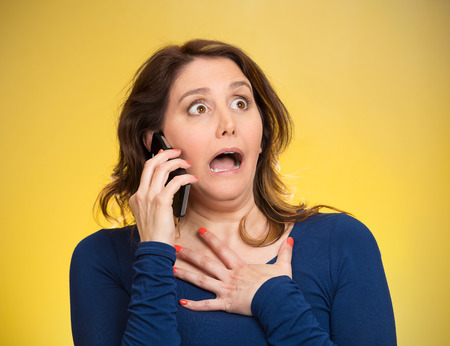 aggravated: Closeup portrait shocked business woman, employee talking on cell phone having unpleasant conversation, receiving shocking news isolated yellow background. Negative emotion facial expression reaction Stock Photo