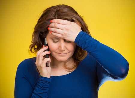 Young sad woman talking on mobile phone upset, depressed, unhappy, worried, isolated yellow background. Negative human emotions, facial expressions, feelings, life perception, reaction. Bad news photo