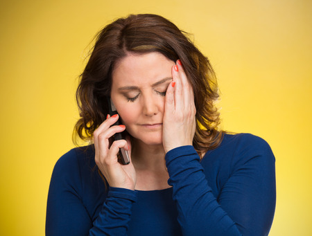 persons: Young sad woman talking on mobile phone upset, depressed, unhappy, worried, isolated yellow background. Negative human emotions, facial expressions, feelings, life perception, reaction. Bad news