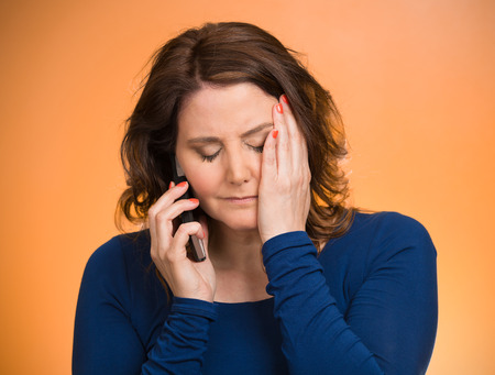 Young sad woman talking on mobile phone upset, depressed, unhappy, worried, isolated orange background. Negative human emotions, facial expressions, feelings, life perception, reaction. Bad news