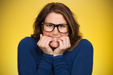 perspiration: Closeup portrait nervous, stressed young woman, employee student biting fingernails looking anxiously, craving for something isolated yellow background. Human emotions, expression feeling body language