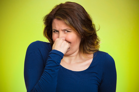 Closeup portrait middle aged woman who covers, pinches her nose with hand looks with disgust, something stinks, bad smell, situation, isolated green background. Human face expressions, body language
