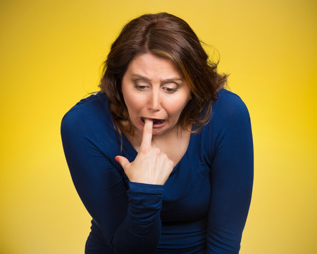 Closeup portrait young woman, annoyed, frustrated fed up sticking fingers in her throat showing she is about to throw up. Case anorexia nervosa, Isolated yellow background. Negative face expression