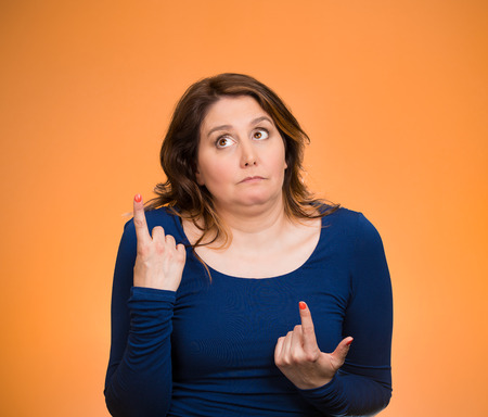 befuddled: Closeup portrait confused young woman pointing in two different directions, not sure which way to go in life, isolated orange background. Negative emotions, facial expressions, feelings, body language